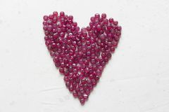 Ruby stones lie on a white table in the shape of a heart. Natural stones ruby, ruby beads. Pink heart of ruby. Love, Valentine. Ruby stones lie on a white table royalty free stock images