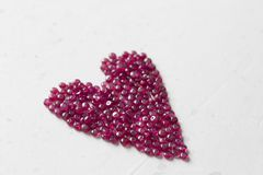 Ruby stones lie on a white table in the shape of a heart. Natural stones ruby, ruby beads. Pink heart of ruby. Love, Valentine. Copy space for your text royalty free stock images