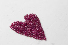 Ruby stones lie on a white table in the shape of a heart. Natural stones ruby, ruby beads. Pink heart of ruby. Love, Valentine. Copy space for your text royalty free stock image