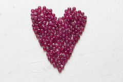 Ruby stones lie on a white table in the shape of a heart. Natural stones ruby, ruby beads. Pink heart of ruby. Love, Valentine. Ruby stones lie on a white table stock photography