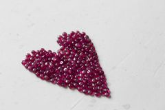 Ruby stones lie on a white table in the shape of a heart. Natural stones ruby, ruby beads. Pink heart of ruby. Love, Valentine. Copy space for your text stock photo