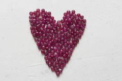 Ruby stones lie on a white table in the shape of a heart. Natural stones ruby, ruby beads. Pink heart of ruby. Love, Valentine. Ruby stones lie on a white table stock image