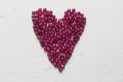 Ruby stones lie on a white table in the shape of a heart. Natural stones ruby, ruby beads. Pink heart of ruby. Love, Valentine. Ruby stones lie on a white table royalty free stock photos