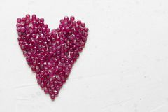 Ruby stones lie on a white table in the shape of a heart. Natural stones ruby, ruby beads. Pink heart of ruby. Love, Valentine. Copy space for your text stock photography