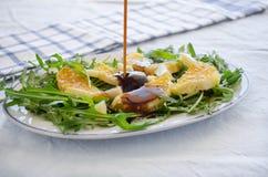 Ruccola-Salat mit Orange, Käse, indischem Sesam und balsamischem Stockfoto