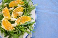 Ruccolasalade met sinaasappel, kaas, sesam en balsemiek Royalty-vrije Stock Afbeeldingen