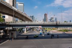 Ruch drogowy i transport w śródmieściu z handlowym budynkiem, niebo pociągiem i chmurnego niebieskiego nieba tłem, zdjęcia royalty free
