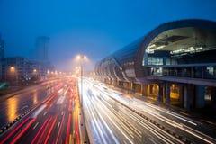 Ruch drogowy z lekkim śladem obok dworca podczas błękitnej godziny po deszczu fotografia stock