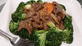 Ruch fertanie dłoniaka wołowina z brokułami na stole wśrodku restauracji zbiory