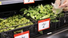 Ruch kupuje gorzkiego melon wśrodku Walmart sklepu kobieta zbiory