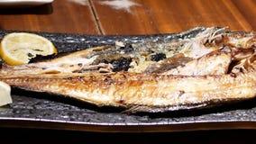 Ruch ludzie je smażącej cytryny na stole i makreli zbiory