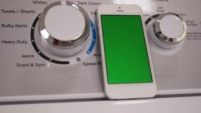 Ruch pokaz płuczki maszyna i zielony parawanowy telefon zbiory
