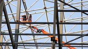 Ruch pracownicy przy wzrostem w dźwignięciu między strukturami metal