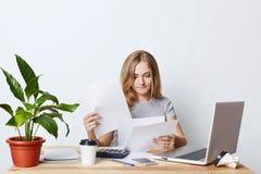 Ruchliwie żeński enterpreneur patrzeje przez dokumentów, siedzi przy stołem w jej gabinecie, pracuje z laptopem, mądrze telefon i Zdjęcia Stock