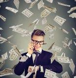 Ruchliwie biznesmen patrzeje wristwatch, opowiada na telefonie komórkowym pod gotówka deszczem Czas pieniądze pojęciem jest Fotografia Royalty Free
