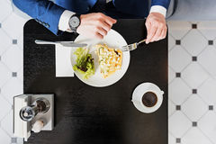 Ruchliwie biznesmen patrzeje zegarek podczas posiłku Zdjęcia Royalty Free