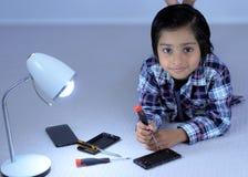 Ruchliwie dzieciaka naprawiania telefon komórkowy z śrubokrętem obrazy royalty free