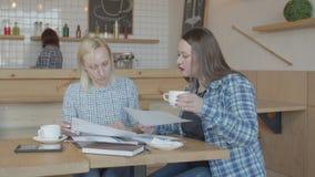 Ruchliwie kobiet freelancers pracuje z papierami w kawiarni zbiory