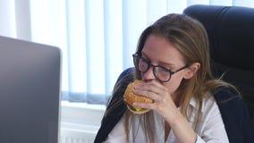 Ruchliwie kobieta robi notatkom w notatniku podczas gdy mieć hamburger zdjęcie wideo