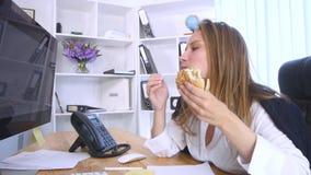 Ruchliwie kobieta używa komputer podczas gdy mieć hamburger zbiory