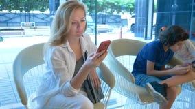 Ruchliwie kobieta używa telefon w hotelowym lobby, jej dzieci siedzą obok ona i także używają telefon obrazy stock