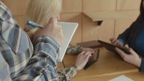 Ruchliwie kobiety używa pastylkę w kawiarni podczas gdy robić rozkazowi zbiory wideo