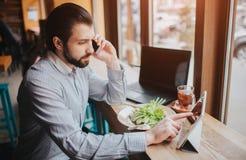 Ruchliwie mężczyzna jest w pośpiechu, no ma czasu, iść jeść i pracować Pracownika łasowanie, pije kawę obraz royalty free