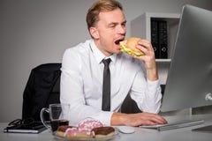 Ruchliwie mężczyzna przy biurowym łasowanie fastem food Zdjęcie Royalty Free