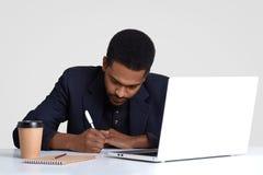 Ruchliwie męski pracownik z ciemną zdrową skórą, pisze puszek informacji w papierach, chwyta pióro, jest ubranym czarnego kostium zdjęcie royalty free