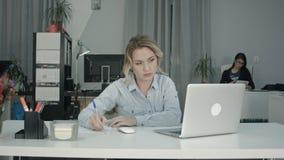 Ruchliwie młoda kobieta pracuje na laptopie w biurze podczas gdy jej coworker używa pastylkę fotografia royalty free
