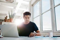 Ruchliwie młody człowiek pracuje w biurze Zdjęcie Stock