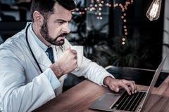 Ruchliwie skoncentrowany student medycyny pracuje z laptopem pije herbaty obrazy stock