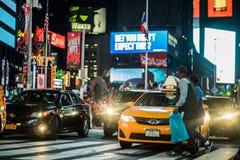 Ruchu drogowego i koloru żółtego Hybrydowe taksówki w times square przy nocą, Manhatt Obrazy Royalty Free