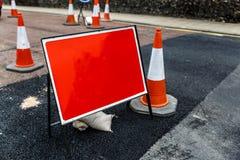 Ruchu drogowego znak z czerwonym tłem obok kilka konusuje Fotografia Royalty Free