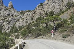 Ruchu drogowego znaka ` Ustępował na nadchodzącym ruchu drogowego ` przy niebezpiecznym obraca dalej halną drogę Fotografia Royalty Free