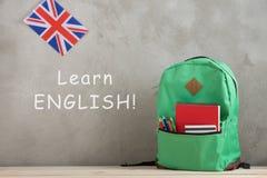 Rucksack, Flagge Großbritanniens und Notizbücher gegen eine Zementwand mit Text ' Lernen Sie Englisch lizenzfreie stockbilder
