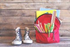 Rucksack mit Schulbedarf auf Holztisch stockbilder