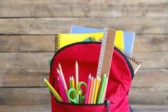 Rucksack mit Schulbedarf auf Holztisch lizenzfreie stockfotografie