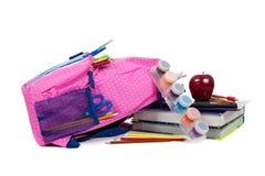 Rucksack mit Schulezubehör auf weißem Hintergrund Lizenzfreie Stockbilder