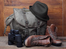 Rucksack with old boots, binoculars and hat on wooden background Royalty Free Stock Photo