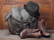 Rucksack with old boots and hat on wooden background Stock Photography