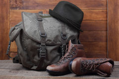 Rucksack with old boots and hat on wooden background Royalty Free Stock Photography