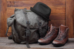Rucksack with old boots and hat on wooden background Stock Photo