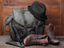 Rucksack with old boots, knife and hat on wooden background Royalty Free Stock Images