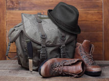 Rucksack with old boots, knife and hat on wooden background Royalty Free Stock Photography