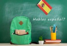 Rucksack, Tafel mit Text ' hablas español' , Flagge des Spaniens, Bücher und Schulbedarf stockbilder
