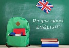 Rucksack, Tafel mit Text ' Sprechen Sie Englisch? ' , Flagge Großbritanniens, Taschenrechner, Bücher und Notizbücher lizenzfreies stockfoto