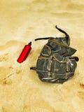 Rucksack- und Kantinenwasserflasche im Sand eines Strandes Stockbild