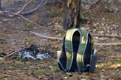 Rucksack und Lagerfeuer im Nadelbaumwald Stockbild