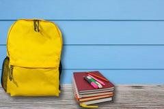 Rucksack und Notizbuch wird auf einen Holztisch mit blauer Wand gesetzt Stockbild
